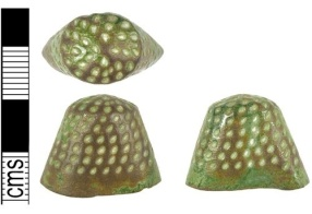 Cast cu-alloy thimble with individually drilled holes dating from the late medieval period.